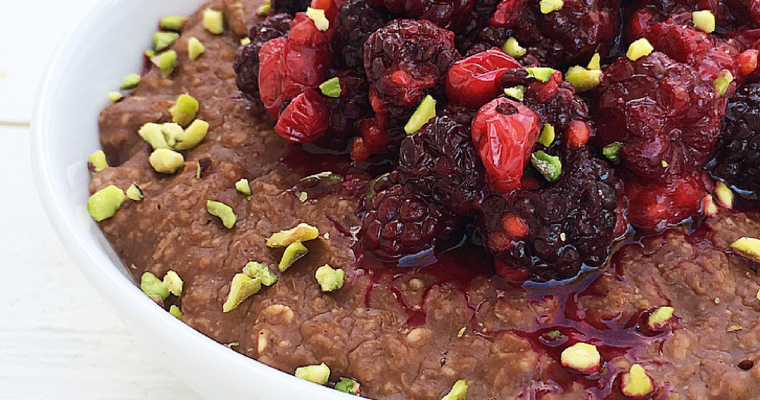 Porridge cacao e nocciole con frutti rossi e pistacchi.