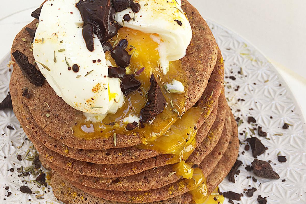 Pancakes speziati di grano saraceno con pomodori, uovo in camicia e cioccolata fondente.